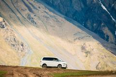Mitsubishi Delica Space Gear driving on off road on summer mountain background Stock Photos