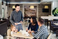Restaurant and holiday concept - waiter giving menu to happy family at cafe Kuvituskuvat