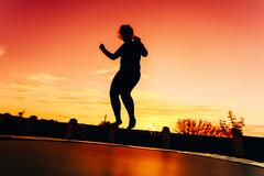 Silhouette Of Beautiful Plus Size Young Woman Girl Jumping On Tr Trampoline Stock Photos