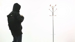 A young man takes off and hangs up the backpack, winter jacket on hanger. Stock Footage