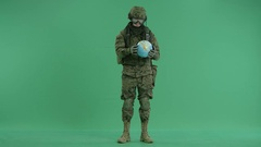 Soldier holding globus at green screen Stock Footage