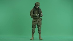 Soldier counting money and looking at camera at green screen Stock Footage