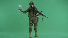 Soldier holding globus and looking at camera at green screen Stock Footage