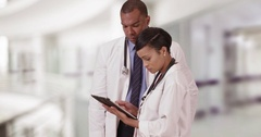 Two black expert medical professionals discuss a patient while on their tablet Stock Footage