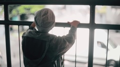 Back view of a little boy leaning on a bridge railing, turning his face to Stock Footage