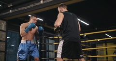 Boxer training punches boxing club 4k video. Fighter blows trainer punch mitts Stock Footage