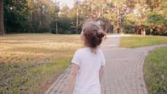 Little girl walking on a road in a park. A bun of fair hair has gold glow. Stock Footage