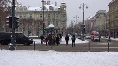 People walking zebra crossing with traffic light and cars on snowy day in winter Stock Footage