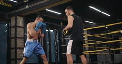 Boxer training uppercut punches in boxing club 4k video. Rrainer punch mitts Stock Footage