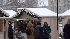 Young woman take selfy near holiday fair kiosk in christmas town. Blizzard snow Stock Footage