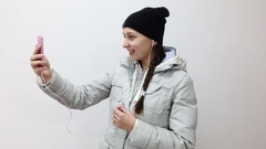 Teenager girl with headphones in ears talking on video call on smartphone. Stock Footage