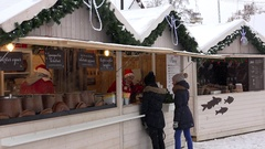 Young girls buying hot drinks from christmas town fair vendor. Blizzard snow Stock Footage