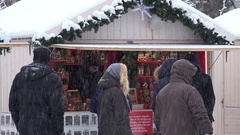 People buy souvenirs in christmas town fair kiosk. Snow blizzard Stock Footage