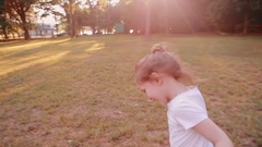 A cheerful little girl runs on a road in a park on a sunny summer day. Back view Stock Footage