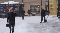 Businessman with phone, yard keeper shovel snow and other people. Blizzard snow Stock Footage