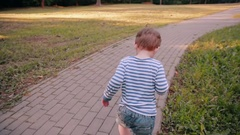 A cute little boy walking on a road in a park on a sunny summer day. Back view Stock Footage