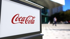 Street signage board with Coca-Cola logo. Blurred office center and walking Stock Footage