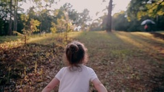 A cheerful little girl running up on a hill in the nature on a sunny summer day Stock Footage