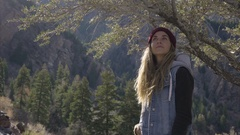 Female Hiker Stands Proud Beneath Tree On Mountain, Then Makes A Funny Face Stock Footage