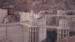 Establishing shot of Hoover Dam with car traffic crossing from Arizona to Nev Stock Footage