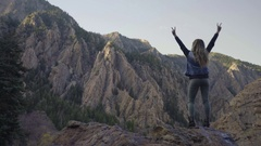 Adventurous Young Woman Stands On Top Of Peak In Mountains, Holds Up Peace Signs Stock Footage