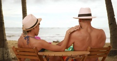 African American couple relax while drinking on the beach Stock Footage