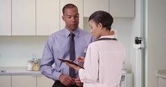 A black doctor advises an African American patient using her tablet Stock Footage
