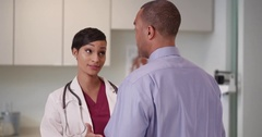 A black doctor advises an African American patient in her office Stock Footage