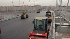Aerial shot of many compactors on new asphalt paved on modern viaduct Stock Footage