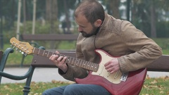 Young rock musician practicing his guitar skills outside Stock Footage