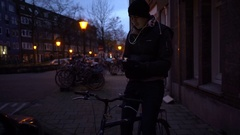 Night illuminated street. Handsome young man at bycicle with headphones using Stock Footage
