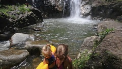 Blond Mother Carries Small Daughter into Mountain River Stock Footage