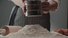 Master chef sifts flour for making dough for spaghetti, close-up, slow motion Stock Footage