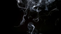 SLOW MOTION: Thin cigarette smoke lifts up on a dark background Stock Footage