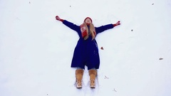 Happy woman making snow angel Stock Footage