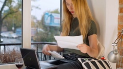 Girl looks surprised while checking her bills, steadycam shot Stock Footage