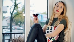 Sad girl drinking wine by the window and thinking about her problems Stock Footage