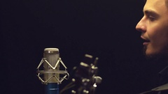 Young musician playing acoustic guitar and singing. Man staying behind mic Stock Footage