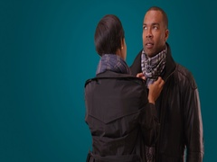 A black woman has fun fixing her boyfriend's scarf on a blue background Stock Footage