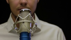 Young caucasian male singer performing at studio with microphone Stock Footage
