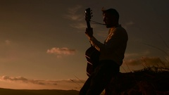 Young attractive male guitarist playing on guitar Stock Footage