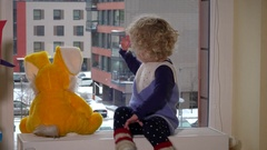 Child little girl sitting by window with bunny friend and looking at snowflakes Stock Footage