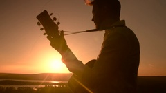 Young attractive caucasian man sitting outdoors and playing guitar at sunset Stock Footage