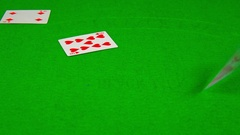 Playing cards falling on green table Arkistovideo