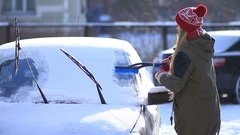 Lady removing snow from windshield with snow brush Stock Footage