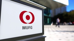 Street signage board with MUFG logo. Blurred office center and walking people Stock Footage