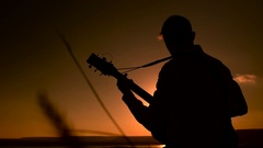 Silhouette of young man sitting outdoors and playing acoustic guitar at sunset Stock Footage