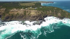 Forward flight above waves breaking on rugged coastal cliffs Stock Footage