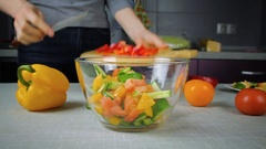 Cook pours in a bowl salad ingredients Stock Footage