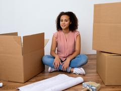Happy woman surrounded by large boxes ready for home relocation Stock Photos